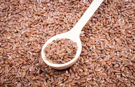 flaxseed: flaxseed on white background with a wooden spoon Stock Photo