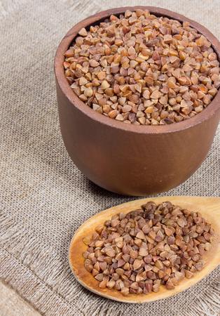 groats: Buckwheat groats and wooden spoon on canvas. Stock Photo