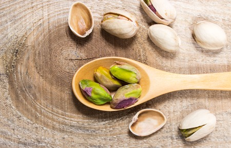 pistachios: Closeup of a pistachios on wooden background. Stock Photo
