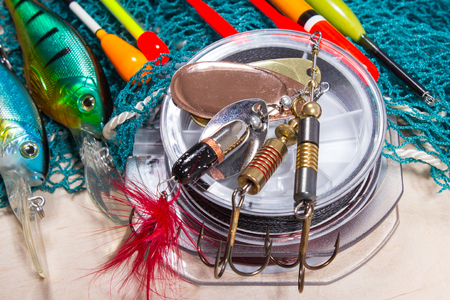 bait, wobbler and fishing accessories on wooden background Stock Photo