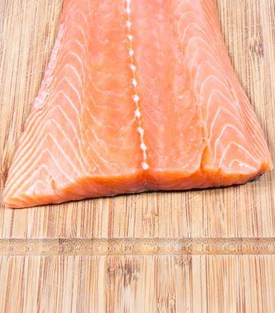 unsaturated: CloseUp on fresh salmon fillet on a wooden background.