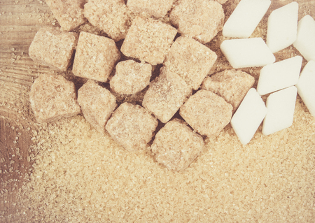 crystal background: Cubes of sugar - brown sugar cane on the wooden background.