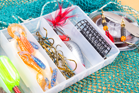 Open storage box with accessories for fishing and fishing baits. Stock Photo