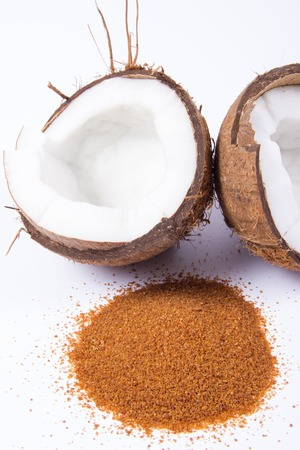CloseUp on a coconut with coconut sugar isolated on white background.