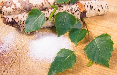 자일리톨 - 당뇨병 환자를위한 설탕 대체품. 나무 배경에 자작 나무 설탕입니다. 스톡 콘텐츠