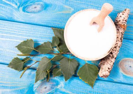 キシリトール - 糖尿病患者の砂糖の代用品。青い木製の背景に砂糖をバーチします。