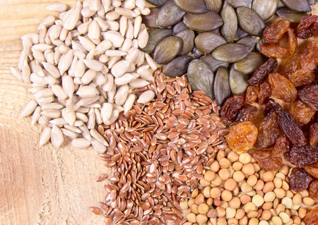 Flaxseed, pumpkin, raisins, lentils and sunflower seeds in wooden spoons. Seeds - a concept of healthy food additives. Stock Photo