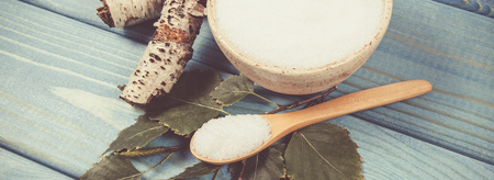 Xylitol - sugar substitute for diabetics. Birch sugar on blue wooden background.