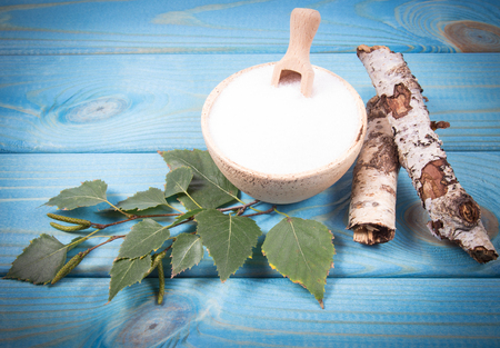 Xylitol - sugar substitute for diabetics. Birch sugar on blue wooden background.