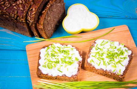 Sandwiches with granulated white cheese and chives. Healthy breakfast concept. Foto de archivo