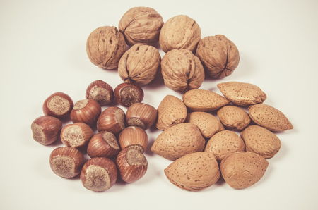 Different types of nuts in a shell on a white background. Hazelnuts, walnuts and almonds.
