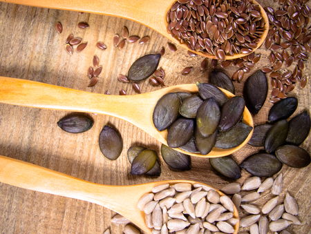 Flaxseed, pumpkin and sunflower seeds in wooden spoons. Seeds - a concept of healthy food additives.