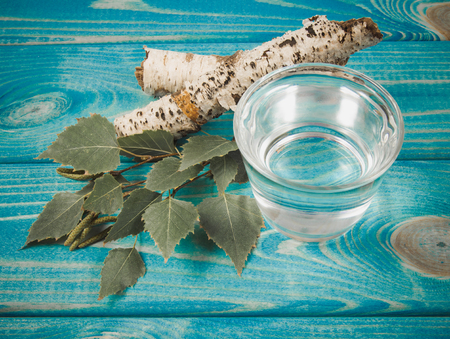 A glass of birch juice on blue wooden background. Close Up. Stock Photo