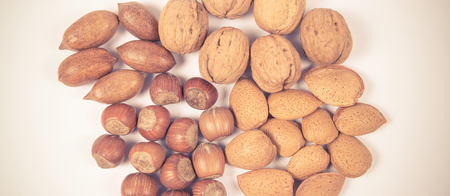Different types of nuts in a shell on a white background. Hazelnuts, walnuts, pecans and almonds.