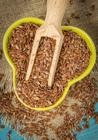 Healthy food. Flax seeds, linseed on kitchen spoon, blue color background. Stock Photo