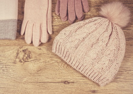 Warm winter knitted clothes: hat, scarf and gloves on a wooden background. Close Up.