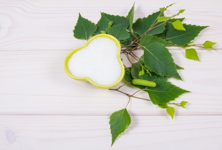 Xylitol - sugar substitute for diabetics. Birch sugar on white wooden background. Stock Photo