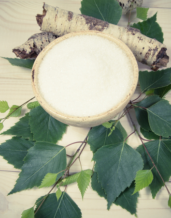 Xylitol - sugar substitute for diabetics. Birch sugar on white wooden background. 版權商用圖片