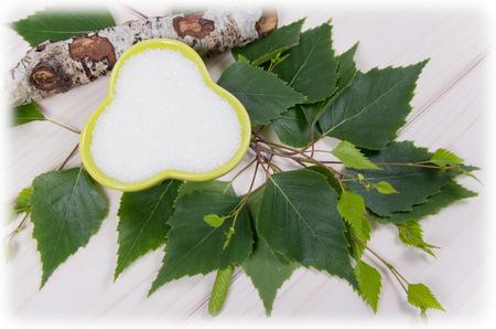 Xylitol - sugar substitute for diabetics. Birch sugar on white wooden background. Zdjęcie Seryjne