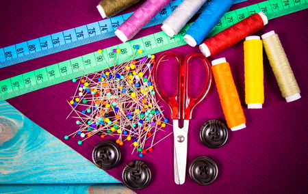Accessories for needlework. Spools of thread, scissors, buttons, measuring tape, sewing supplies.