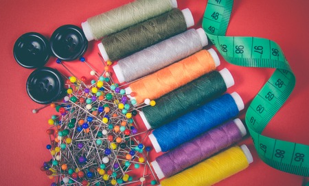 Accessories for needlework. Spools of thread, buttons, measuring tape, sewing supplies. Stock Photo