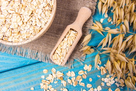 Oat and oatmeal on the wooden background. Healthy eating concept.