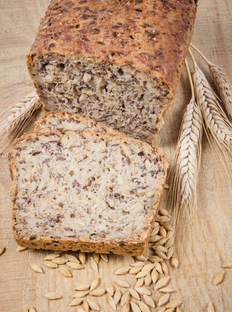 Multi-grain bread on a wooden background. The source of fiber, complex carbohydrates, B vitamins and minerals. 免版税图像