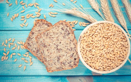 Multi-grain bread on a wooden background. The source of fiber, complex carbohydrates, B vitamins and minerals. Reklamní fotografie