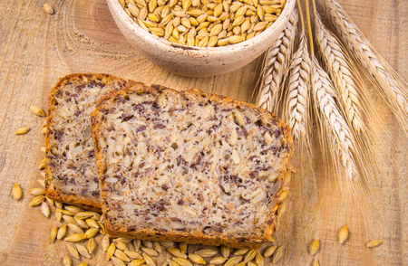 Multi-grain bread on a wooden background. The source of fiber, complex carbohydrates, B vitamins and minerals. Stock Photo