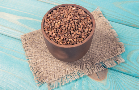 Buckwheat in a ceramic bowl on wooden table. Conception of healthy eating.