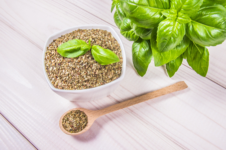 Fresh and dried basil - a component of dishes. Wooden background.