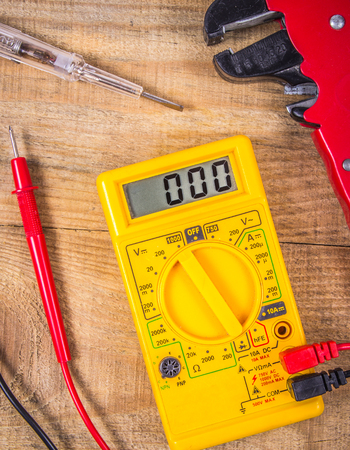 Electrician tools. Electric tester and other tools on a wooden background. The concept of repair and DIY. Banque d'images