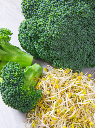 Broccoli sprouts as an ingredient of a healthy diet. A bright wooden background.