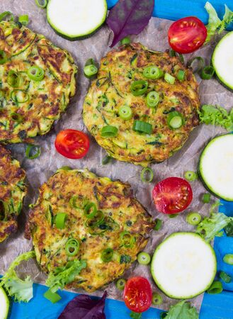 Vegetarian food - zucchini fritters on wooden background.