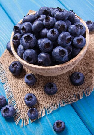 Fresh huckleberry in a bowl on a wooden background. Source of vitamins.