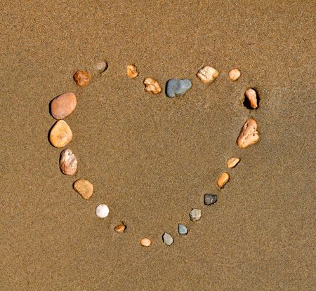 Pictogram. Heart from a pebble on sand