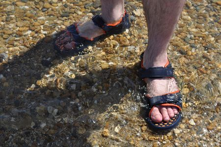hairy legs: legs of the person, costing in water on beach Stock Photo