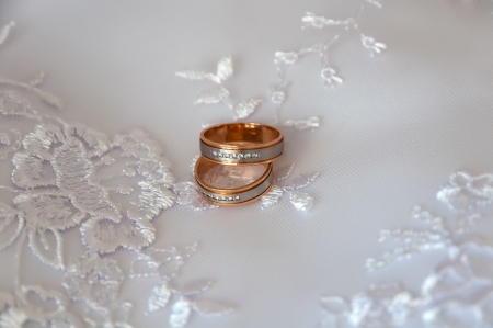 Two Wedding rings on a background of dresses