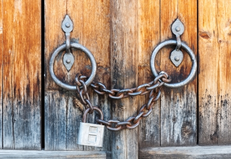 Closed lock with a chain on an old wooden door