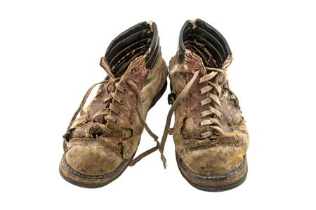 A pair of old dirty boots isolated on white background Stock Photo