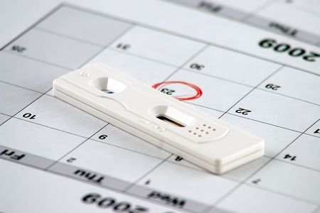 Pregnancy test laying on a calendar with a circled date photo