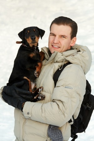 man with a backpack and with a puppy of a terrier on hands against snow. Stock Photo