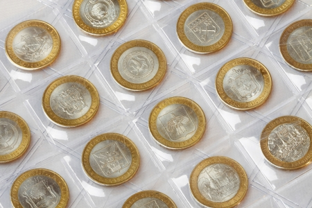 Collection of anniversary coins rubles in a klyasser on a white background