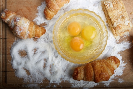 The broken eggs and baking on the wooden board poured by a flour and sugar.