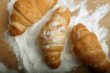 Three croissants on a board with a flour, a horizontal.
