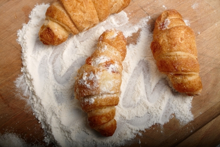 Three croissants on the board sprinkled with a flour Stock Photo