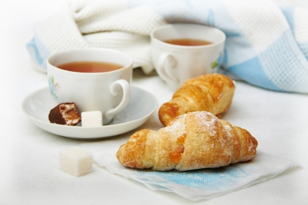 Two cups of tea with croissants on the desktop, a white-blue tonality