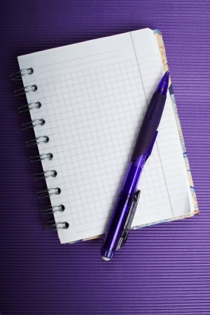 The ruled notepad with a pencil on a violet corrugated background.
