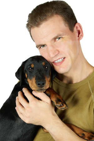 The man (Popov Dmitry) in a green t-shirt embraces a puppy of a Jagdterrier, a white background.