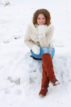 The pretty girl in a light sheepskin coat, jeans and mittens sits on snow, smiling